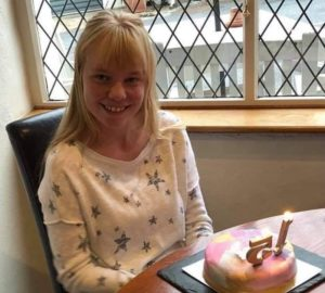 Girl with a birthday cake in front of her